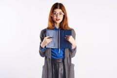 La giovane bella donna in vetri sugli antecedenti bianchi tiene un organizzatore, insegnante, insegna a, Fotografie Stock