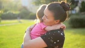 La giovane bella madre che abbraccia e che conforta sua figlia del bambino, mamma abbraccia il bambino, donna lenisce la ragazza video d archivio