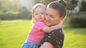 La giovane bella madre che abbraccia e che conforta sua figlia del bambino, mamma abbraccia il bambino, donna lenisce la ragazza stock footage
