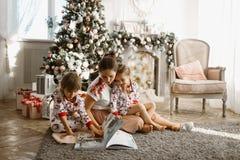 La giovane bella madre con due piccole figlie si siede sul tappeto ed ha letto il libro vicino all'albero del nuovo anno con i re immagini stock