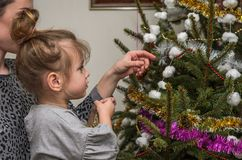 La giovane bella madre con sua figlia affascinante si agghinda l'albero di Natale delle ghirlande e dei giocattoli che conserva i Fotografia Stock