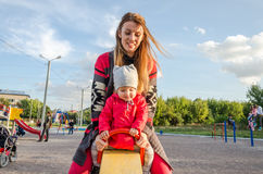 La giovane bella madre in un maglione è giocante e guidante su un'oscillazione con la sua piccola figlia del bambino in un rivest Immagine Stock Libera da Diritti