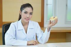La giovane bella protesi dentaria della tenuta del dentista della donna ha fuso il modello Fotografia Stock Libera da Diritti