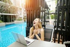 La giovane bella ragazza è molto soddisfatta del computer portatile vicino allo stagno il giorno soleggiato Fotografia Stock Libera da Diritti