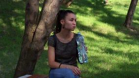 La giovane bella ragazza apre una bottiglia di plastica con acqua e beve l'acqua lei video d archivio