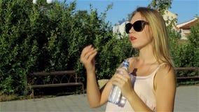 La giovane bella ragazza beve la bottiglia dell'acqua, all'aperto stock footage