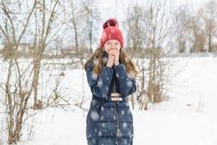 La giovane bella ragazza bionda respira sulle sue mani per riscaldarle nel parco sotto neve lanuginosa molle fotografia stock libera da diritti