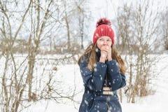 La giovane bella ragazza bionda respira sulle sue mani per riscaldarle nel parco sotto neve lanuginosa molle immagini stock libere da diritti
