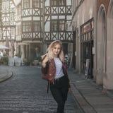 La giovane bella ragazza bionda sta camminando lungo la vecchia st dell'europeo fotografia stock