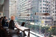 La giovane bella ragazza bionda utilizza il computer portatile ed il telefono mentre lavora il viaggio Fotografia Stock