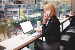 La giovane bella ragazza bionda utilizza il computer portatile ed il telefono mentre lavora il viaggio che si siede in caffetteri Fotografie Stock