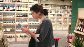 La giovane bella ragazza castana seleziona una bottiglia di vino dallo scaffale per leggere un'etichetta su  stock footage