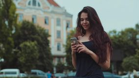 La giovane bella ragazza castana sta fuori, guarda intorno, mentre aspetta qualcuno utilizza il suo telefono Umore positivo video d archivio