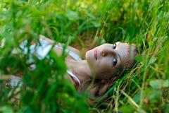 La giovane bella ragazza dello slavo con capelli lunghi e l'abbigliamento etnico dello slavo si trova nell'erba in una foresta de Immagine Stock