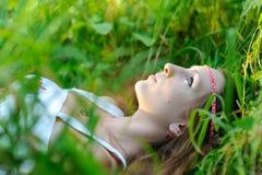 La giovane bella ragazza dello slavo con capelli lunghi e l'abbigliamento etnico dello slavo si trova nell'erba in una foresta de Fotografie Stock