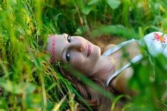 La giovane bella ragazza dello slavo con capelli lunghi e l'abbigliamento etnico dello slavo si trova nell'erba in una foresta de Fotografia Stock