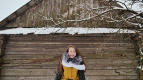 La giovane bella ragazza divertendosi la neve di lancio, posante sulla macchina fotografica nell'inverno copre su fondo della cas stock footage