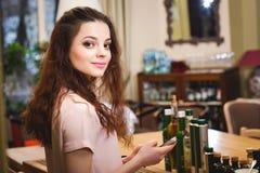 La giovane bella ragazza esamina il telefono a casa nella cucina Immagini Stock