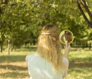 La giovane bella ragazza esamina lo specchio nel parco Concezione della sfuocatura e di morbidezza Fotografia Stock