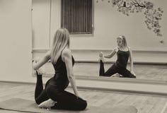 La giovane bella ragazza fa l'allungamento degli esercizi davanti alla m. Fotografia Stock Libera da Diritti