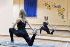 La giovane bella ragazza fa l'allungamento degli esercizi davanti alla m. Fotografie Stock