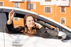 La giovane bella ragazza guarda dalla finestra di automobile, nelle mani delle sue chiavi dell'automobile, acquisto felice immagine stock