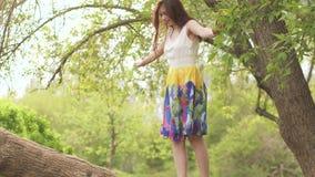 La giovane bella ragazza ha scalato un albero ed ha camminato lungo un ampio ramo Castana in un vestito luminoso sta divertendosi video d archivio