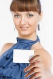 La giovane bella ragazza mostra un biglietto da visita Immagine Stock