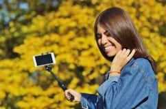 La giovane bella ragazza nel vestito del denim prende il selfie che cammina nel parco della città in autunno fotografia stock libera da diritti
