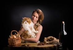 La giovane bella ragazza nelle prendisole da tela si siede ad una tavola di quercia con il gatto persiano rosso notevole sulle ma Fotografie Stock