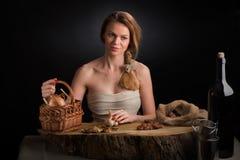 La giovane bella ragazza nelle prendisole da tela si siede ad una tavola di quercia con le cipolle vicine disponibile del canestr Fotografie Stock