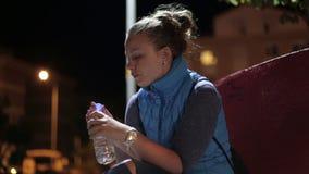 La giovane bella ragazza parla e beve l'acqua da una bottiglia video d archivio