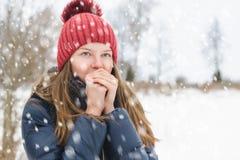 La giovane bella ragazza respira sulle sue mani in modo che sia più caldo, sotto neve lanuginosa molle un giorno di inverno immagine stock libera da diritti