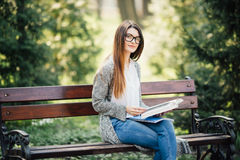 La giovane, bella ragazza seria che tiene un libro aperto, ha letto il parco di verde dell'estate del fondo Immagine Stock