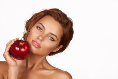 La giovane bella ragazza sexy con capelli ricci scuri, le spalle nude ed il collo, tenenti la grande mela rossa per godere del gu Immagini Stock