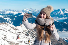 La giovane bella ragazza si è fotografata sul telefono nell'inverno nelle montagne fotografia stock