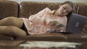 La giovane bella ragazza si siede in sofà di cuoio che parla dal telefono cellulare, esaminante il computer e contante i contanti video d archivio