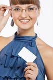 La giovane bella ragazza sorridente mostra un biglietto da visita Fotografia Stock Libera da Diritti