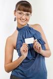 La giovane bella ragazza sorridente mostra un biglietto da visita Fotografie Stock