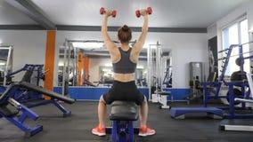 La giovane bella ragazza sportiva che fa la stampa della spalla con le teste di legno che si esercita mentre si siede sugli sport video d archivio
