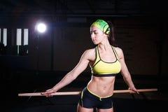 La giovane bella ragazza sta esercitandosi nella palestra Tiene un bastone sopra il suo si dirigono verso i muscoli di trinorvki  Fotografia Stock Libera da Diritti