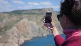 La giovane bella ragazza sta prendendo le immagini sul telefono di bello paesaggio delle montagne e del mare HD, 1920x1080 video d archivio
