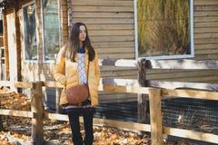 La giovane bella ragazza sta vicino al di legno recinta lo zoo della città Fotografia Stock