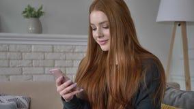 La giovane bella ragazza teenager dai capelli rossi utilizza uno smartphone, sorridendo, mandando un sms, fare scorrere, swiping, archivi video