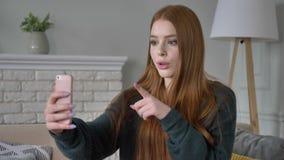 La giovane bella ragazza teenager dai capelli rossi utilizza uno smartphone, la video chiacchierata, la comodità domestica nei pr stock footage