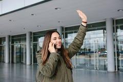 La giovane bella ragazza turistica all'aeroporto o vicino al centro commerciale o alla stazione chiama un taxi o la conversazione Fotografia Stock Libera da Diritti