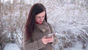 La giovane, bella ragazza, in un cappotto, in un parco dell'inverno, scrive un messaggio video d archivio