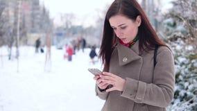 La giovane, bella ragazza, in un cappotto, in un parco dell'inverno, scrive un messaggio archivi video