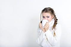 La giovane bella ragazza in una tazza bianca della sciarpa Fotografia Stock