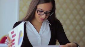 La giovane bella ragazza in vetri freelance lavoro archivi video